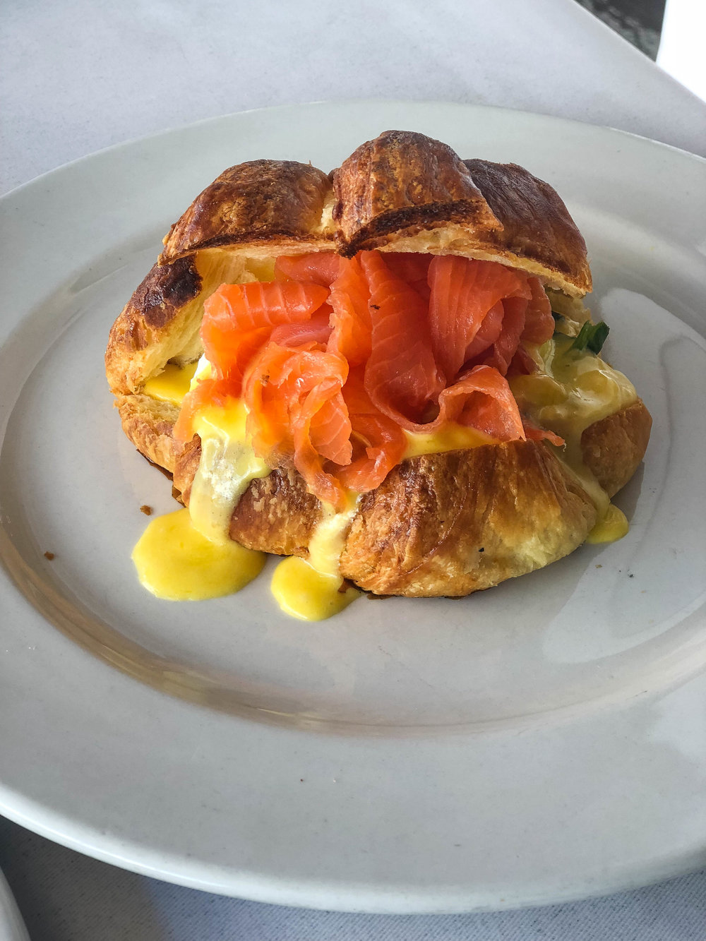 Breakfast croissant with smoked salmon, hollandaise, and scrambled eggs