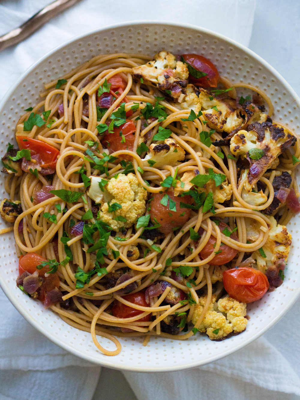 Browned Butter Spaghetti with Roasted Cauliflower is my absolute favorite pasta dish! With a rich browned butter and garlic sauce, juicy cherry tomatoes, sweet caramelized cauliflower and briny capers! So many flavors packed into one bowl of pasta! #pasta #spaghetti #roastedcauliflower #roastedvegetables #brownbutter #healthyrecipe
