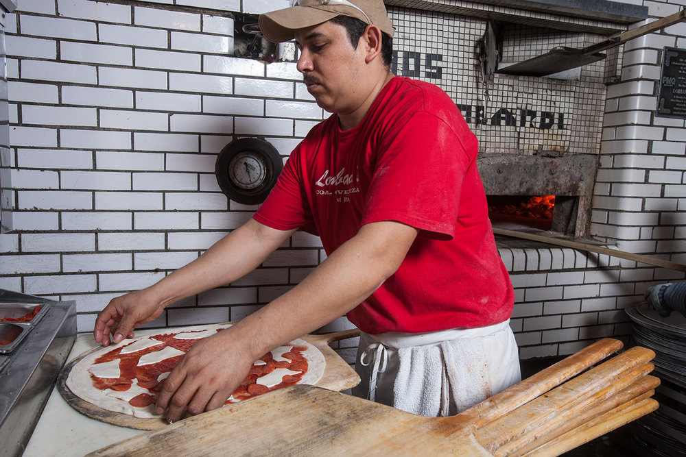 On its surface, a Lombardi's pizza is a simple thing: dough, tomatoes, fresh mozzarella, and basil...