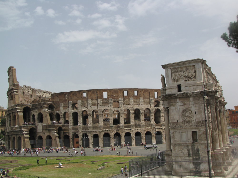 Roman Colosseum. At the right is the Arch of Constantin