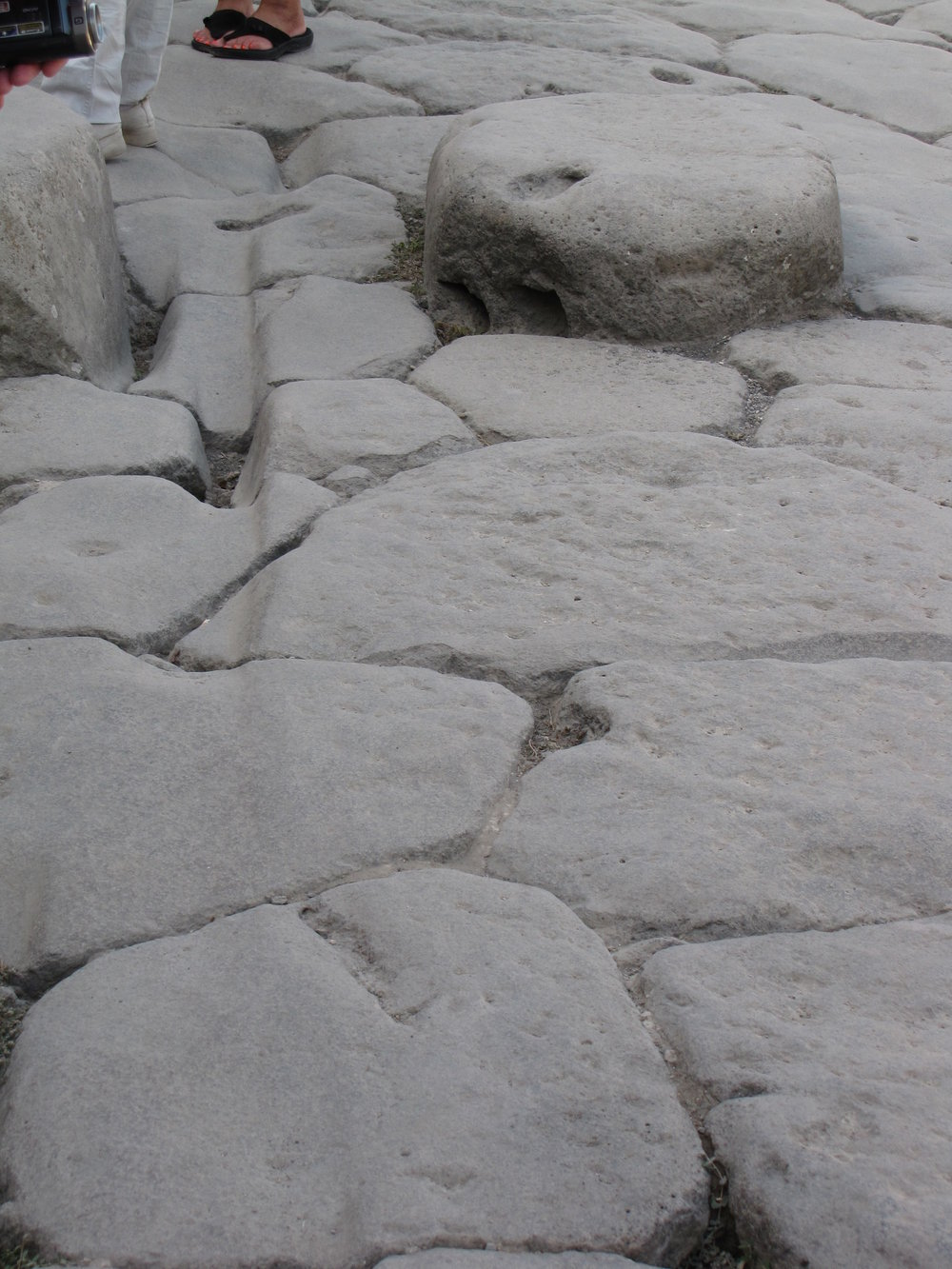 A street in Pompeii—look closely to see the stepping stones to avoid water and waste in the streets and the chariot ruts carved into the stones