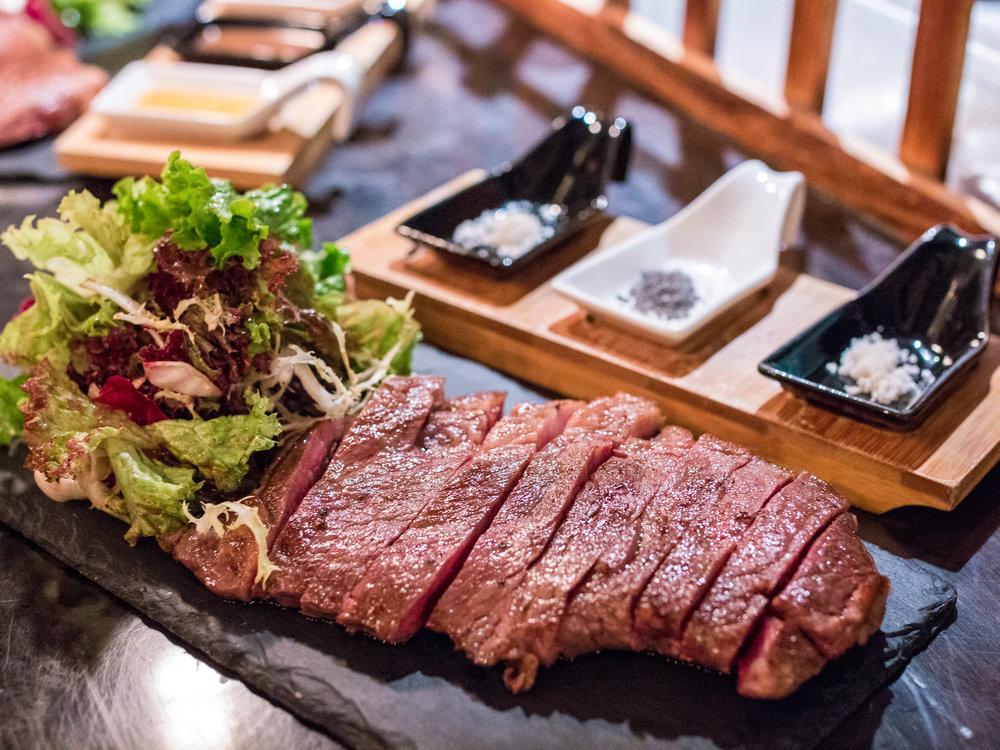 TAJIMA M4-5 AUSTRALIAN WAGYU RIBEYE   Wagyu Beef are raised as free range cattle in a clean air environment and graze on an abundance of natural grasses due to the location of the propertise in high annual rainfall areas in Eastern Australia.It guaranteed to be free of hormones and growth promotents.  Rating: 9/10 -- This is simply my favorite cut from the cow cow. A small attached fat gives the flavor to the entire strip. It is rich and smooth on the longer end. This place does offer very fresh variations of this and I was not disappointed by their choice.   Where It's Cut From: The front end of the Longissimus dorsi, from the Rib primal of the steer. The further towards the head of the steer you get, the more of the Spinalis muscle you'll find in your steak—that's the cap of meat that wraps around the fatter end of the steak.    What It Tastes Like: Highly marbled with a large swath of fat separating the Longissiumus from the Spinalis. Fat is where a lot of the distinctive flavor of beef comes from, making ribeye one of the richest, beefiest cut available. The central eye of meat tends to be smooth textured with a finer grain than a strip steak, while the Spinalis section will have a looser grain and more fat. Many people (myself included) consider the Spinalis to be the absolute tastiest quick-cooking cut on the cow.