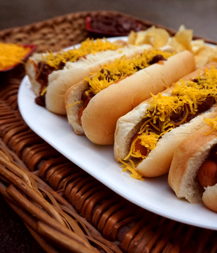 Vegan chili dog sauce on vegan dogs and vegan cheese.