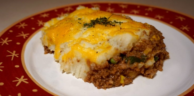 Side view of a slice of vegetarian shepherd's pie no lentils, on a red and white plate.