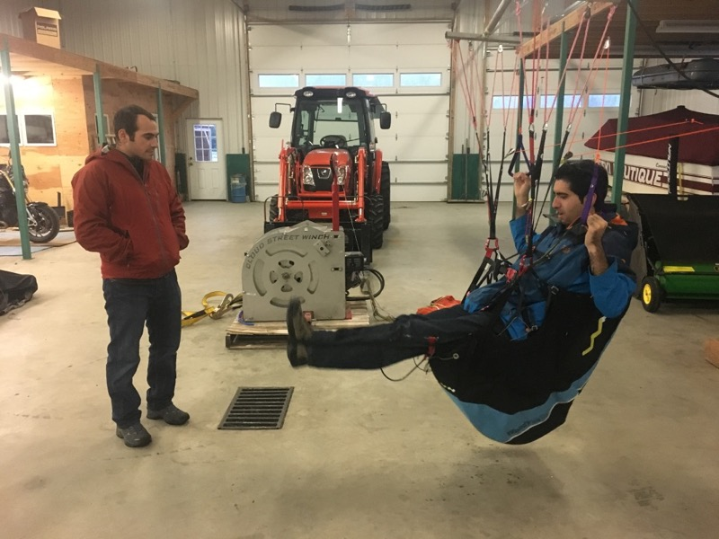 Calef guides a student through harness adjustments while hanging in a paraglider simulator.