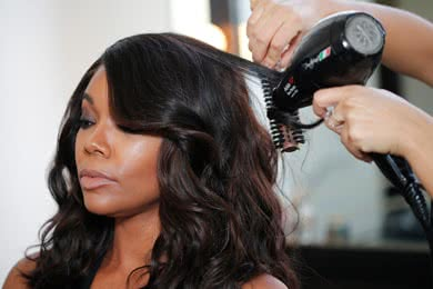 - STEP 4Switch to a smaller round brush and continue through the rest of the head, wrapping the hair from the top of the strand down the brush to the ends to create elongated curls. Dry with tension.