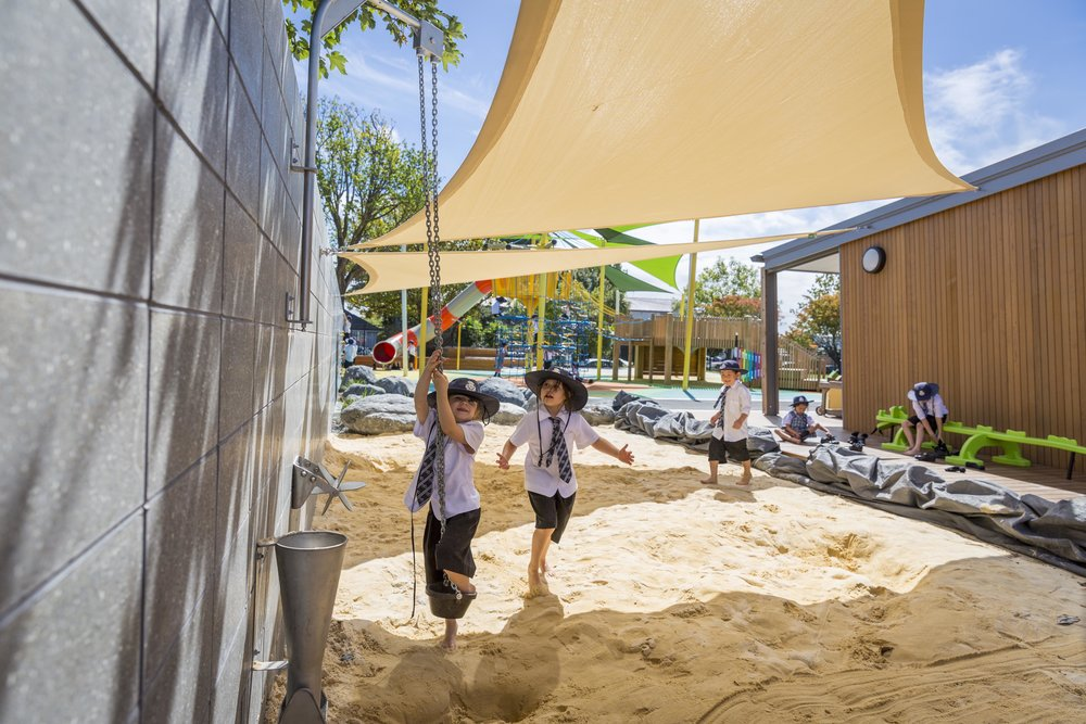 Shade sails which shelter the sandpit are supported by the concrete wall.