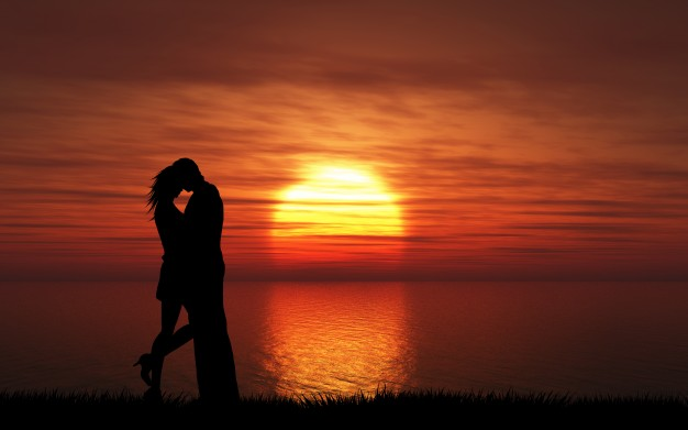 Couple on a beach at sunset by Kjpargeter via Freepik.com