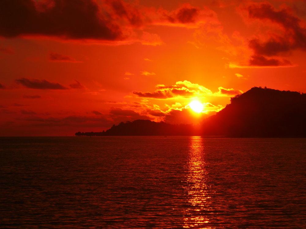 Watching the sun set from behind To'opua from Matira Beach