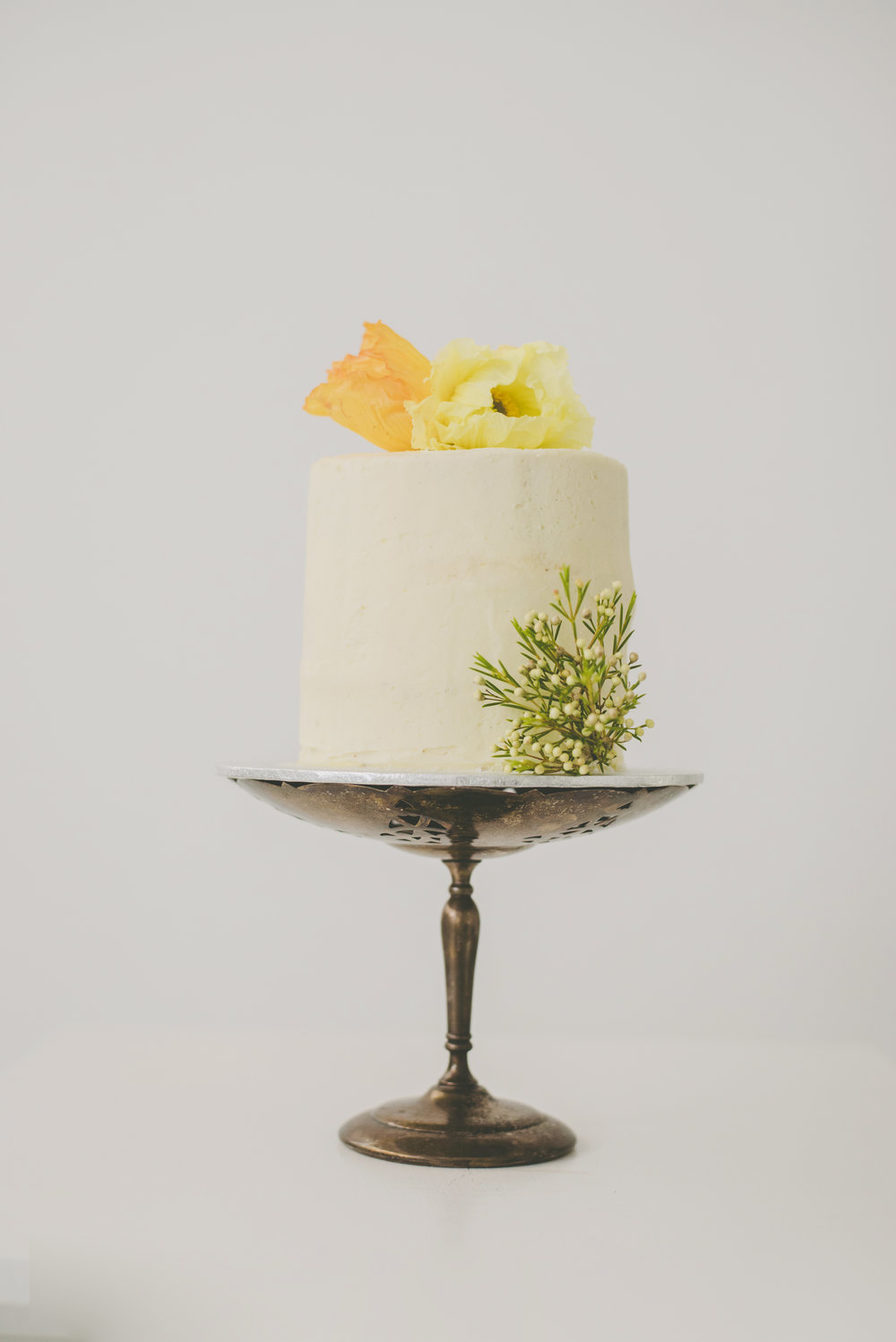 Lemon curd filled chocolate and vanilla cake with american buttercream and fresh poppies