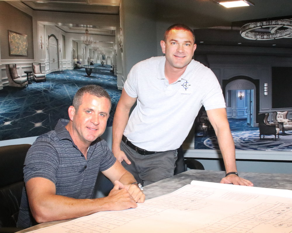 Barry connor, founder and CEO (left, seated) and Craig gaskins, founder and COO (right, standing) at CGU's office in Naples, FL