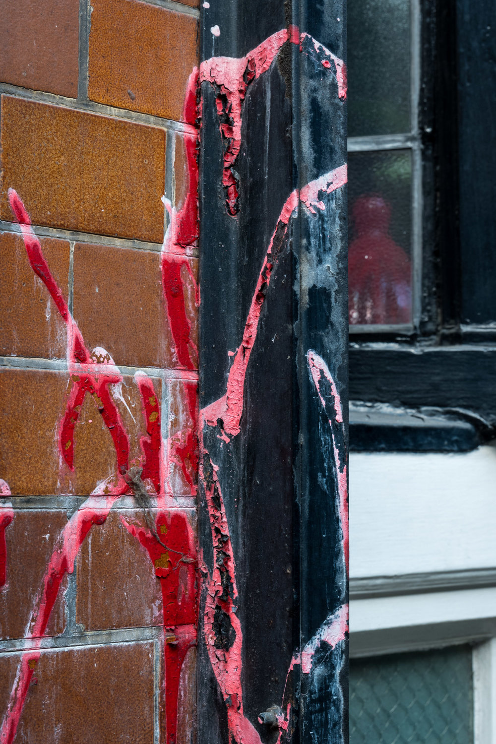 Red Paint on a Wall and Drainpipe