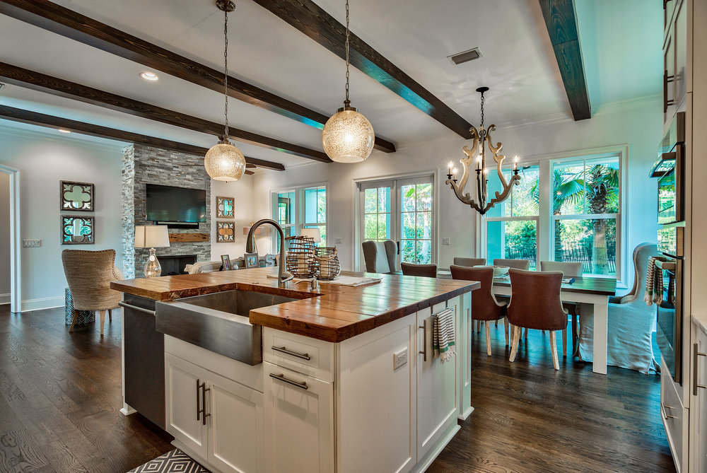 Custom home with exposed wood beams, wood counter top on island and wood flooring