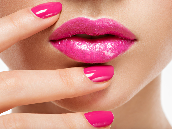Closeup of woman with hot pink lipstick and nails