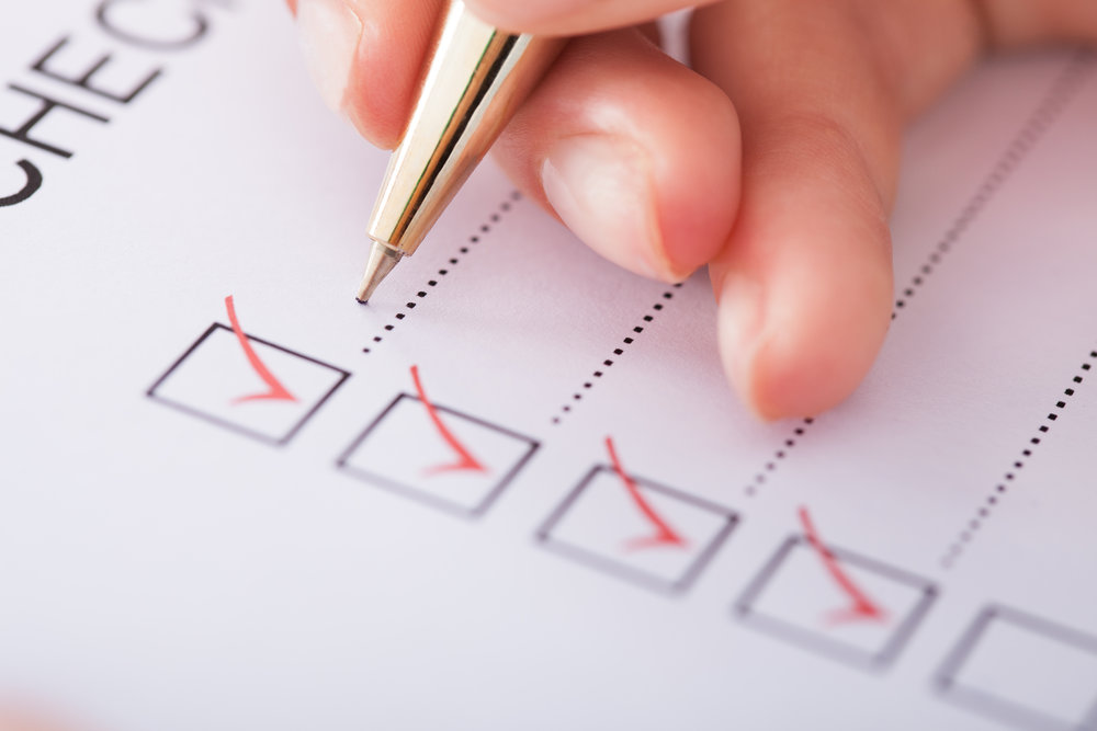 MISSION-ASSURANCE-cropped-image-of-businesswoman-writing-on-checklist-205981180.jpg