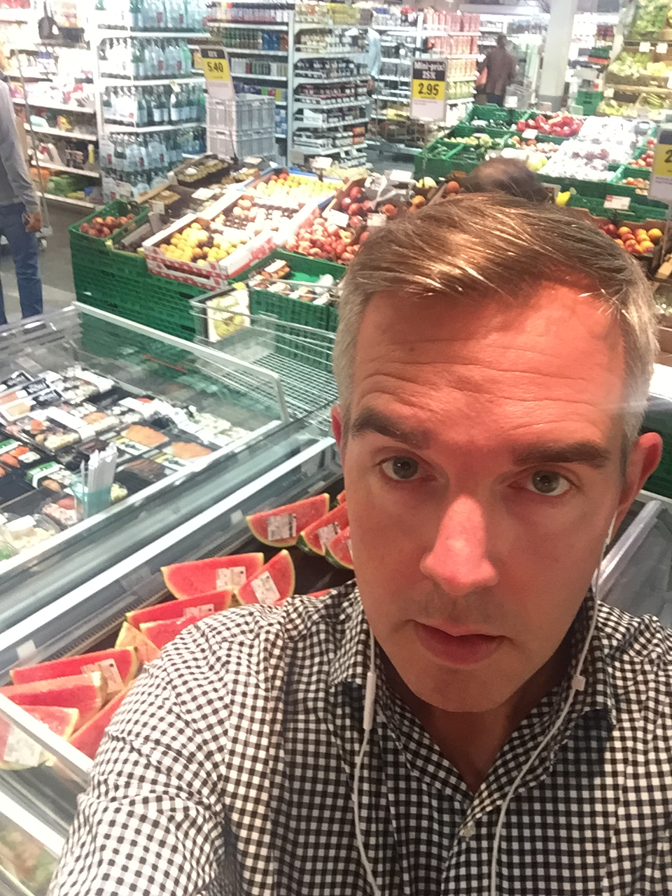 Ben listens in Geneva, Switzerland, while shopping for watermelon.
