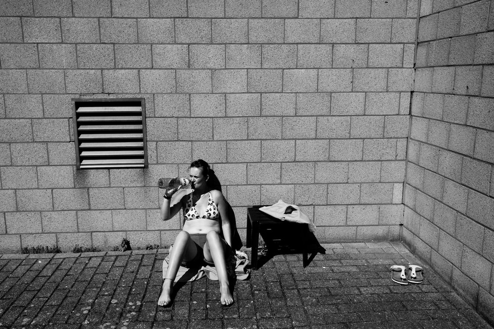 A female prisoner sunbathing at the women's prison in Berkendaele, in Brussels. This courtyard is located next to a men's prison, whose cells offer a direct view on the women's courtyard. Women enjoy mocking men or expose themselves to their sight. Brussels, Belgium - July, 2011