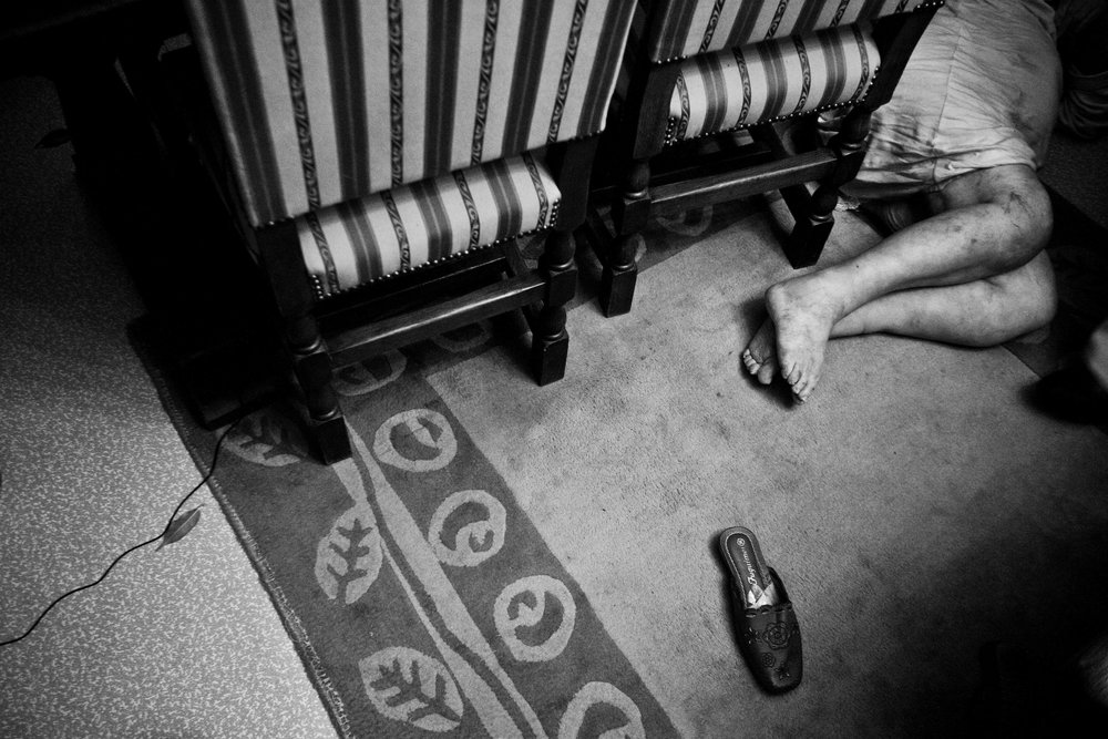 An old women is alive and lying on the floor of her flat in Molembeek. The cops were called for a non response old women, she felt from her chair, and couldn't wake up. Belgium on February 2010.