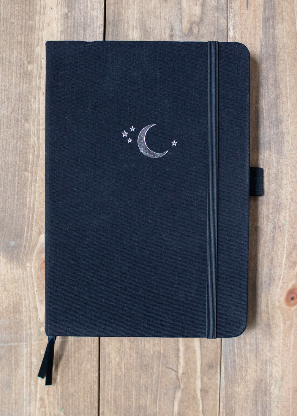"""The details: - The notebook measures 5.75″ x 8.25"""" and features silver gilded edges, a black linen cover, elastic closure, pen loop and two bookmarks."""