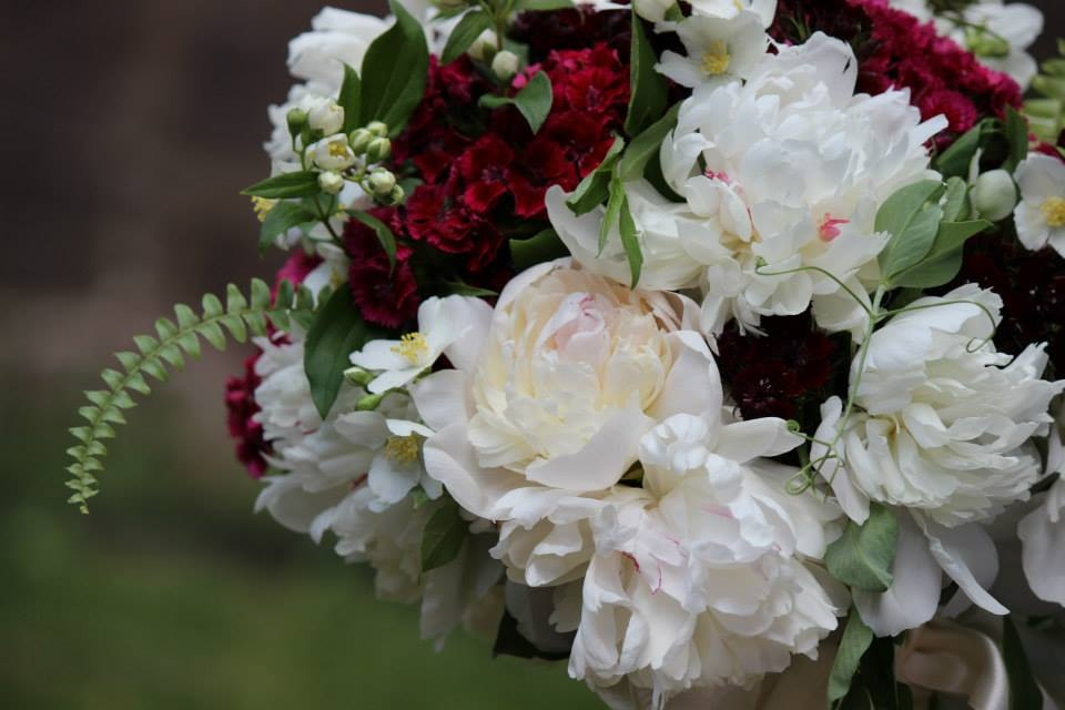 Red and white wedding bouquet with peonies and fern