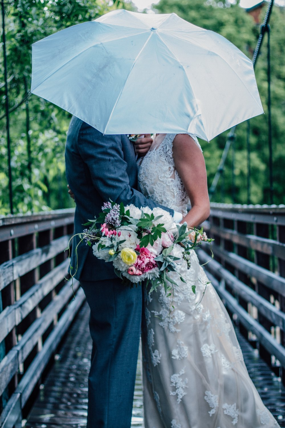 Wedding bouqet with peonies, couple under umbrella
