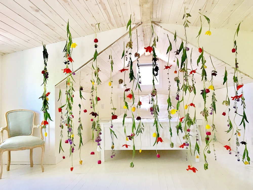 hanging garden with tulips and other spring flowers in white bedroom, floral installation