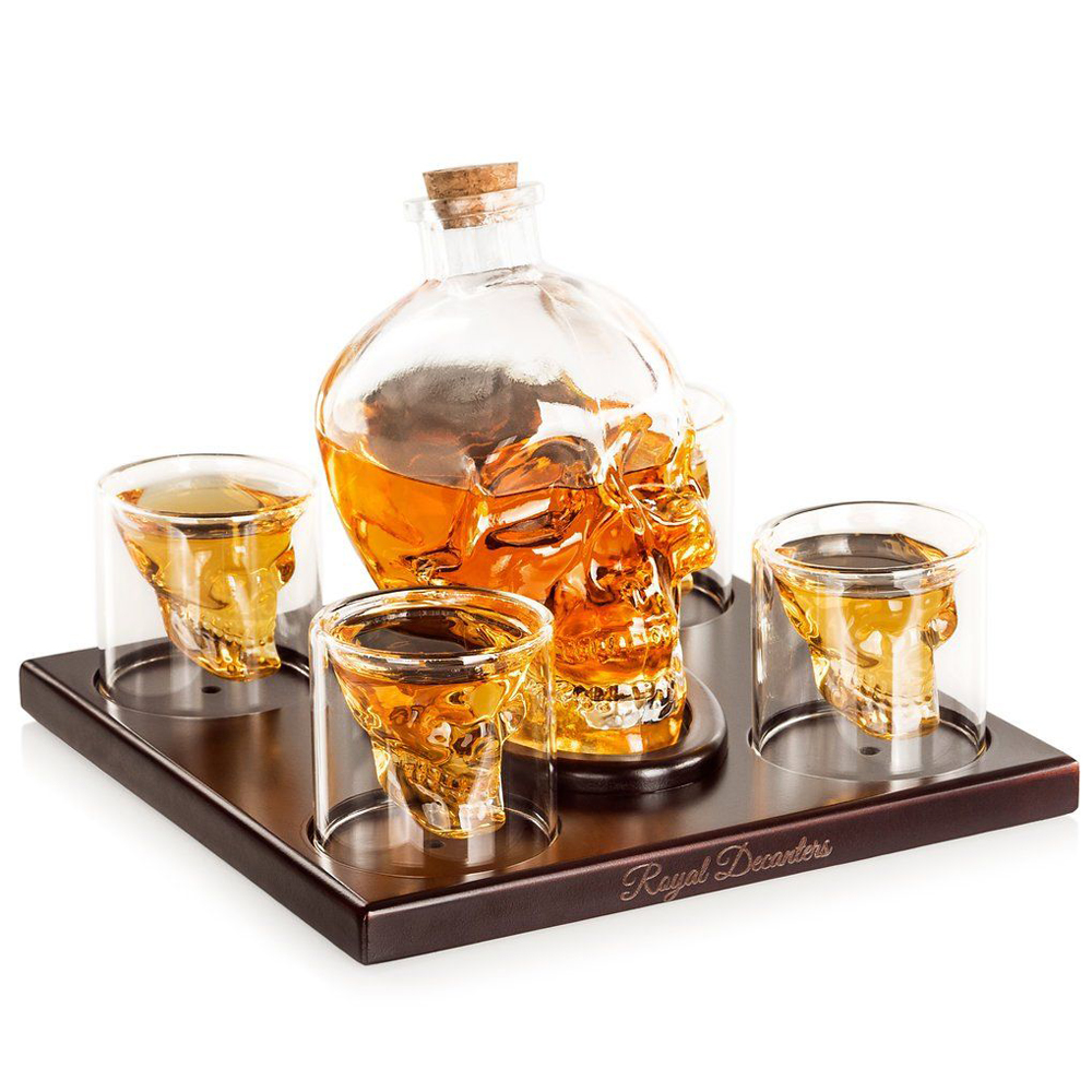 Skull Shaped Glass Decanter - Treat your liquor with the artisan crafted Skull Shaped Whiskey Decanterby the Royal Decanters. The glass can contain 750ml of beverage and comes with 4 bar glasses. In addition to the eye-catching details, the decanter works for any liquid. Serve your friends in style with the Skul Glass Decanter.