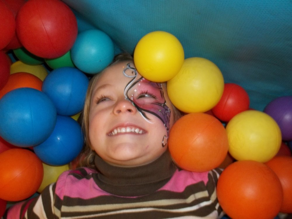 Sophia with face paint in ball pit.JPG