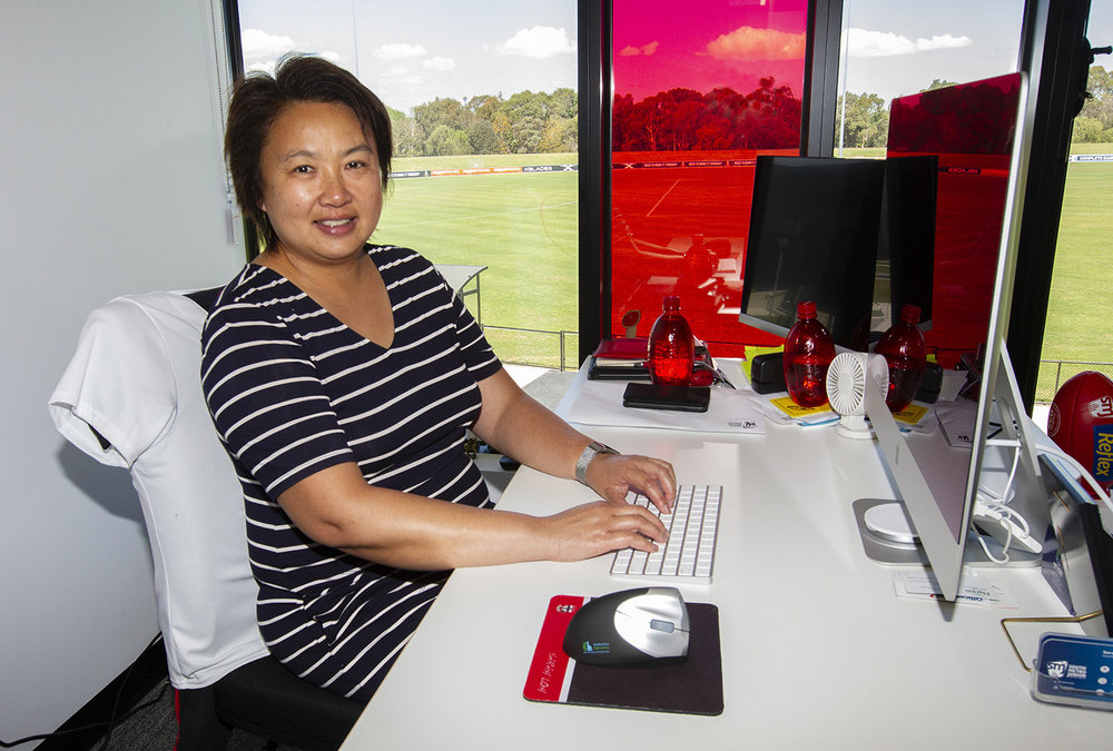 Photographed at her office desk, where Sarah Loh runs the South Metro Junior Football League. Playing with the Warriors was a highlight of her lifelong involvement in sports and football.