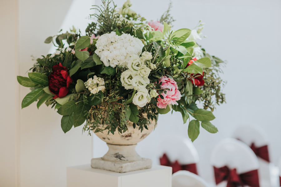Two large urn arrangements welcomed guests as they entered the ceremony room which was a bright, white space.