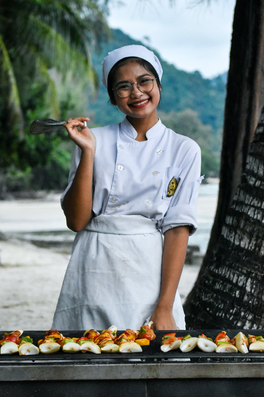 ….    First year student Ying grills on the beach around sunset at  Barali Beach Resort  in Koh Chang, Thailand.    ..    นักศึกษาปีหนึ่ง หญิง ย่างเนื้อบนชายหาด ก่อนอาทิตย์ลับขอบฟ้า ณ บาราลีรีสอร์ท เกาะช้าง    ….