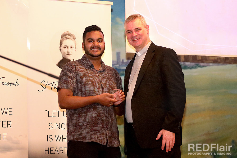 Tishan (left) receiving the Youth Ministry Community Life Award 2019 from Archbishop Peter A. Comensoli (right).