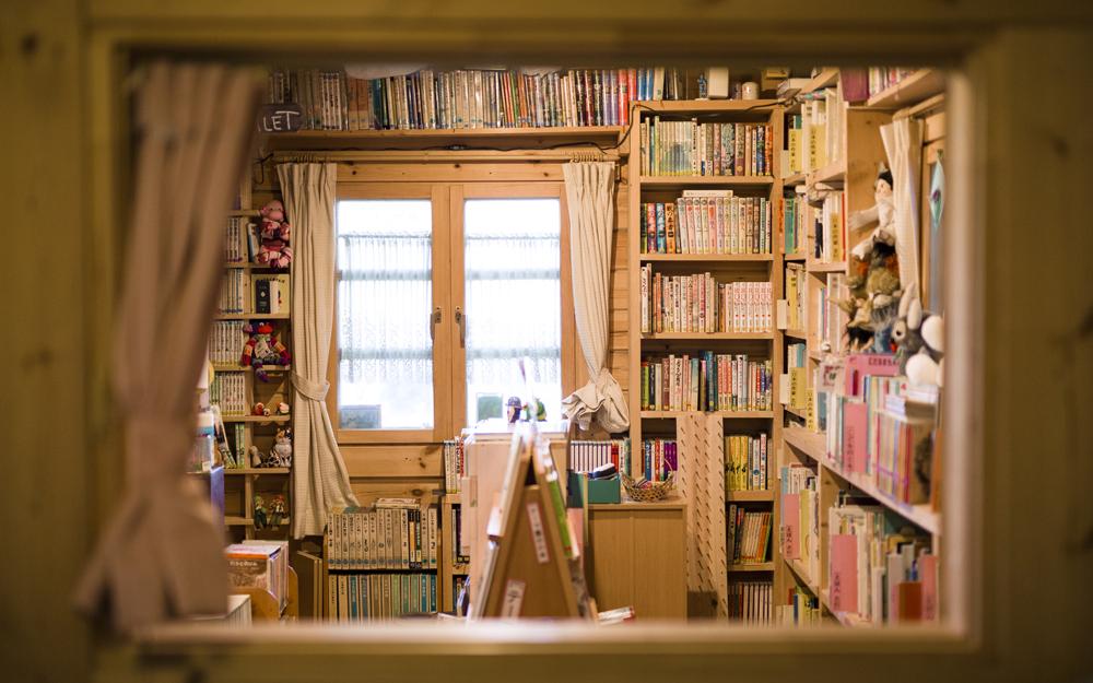 フィンランド製のログハウスの中は、壁一面の本棚に絵本、漫画、YA文学など約1万冊の本たちがぎっしりと詰まった本好きにはたまらない空間。子どもたちの中には、おひさま文庫が公的な図書館だと思っている子もいるとか。この木枠の窓は人形劇カスパーシアターを行えるようにと特注で作ってもらったもの