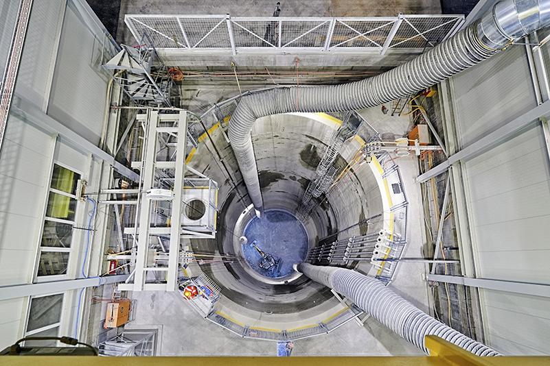 Neun Monate nach Beginn der Arbeiten wurde der Aushub der beiden neuen Schächte für den  High-Luminosity LHC  abgeschlossen. Am Standort des  CMS-Experiments  (LHC-Punkt 5) wurde noch vor Ende 2018, ein 60 Meter tiefer Schacht mit einem Durchmesser von 11 Metern vollständig freigelegt. Auf dem Bild zu sehen ist das Gelände des  ATLAS-Experiments  (LHC-Punkt 1), auf welchem ein 62 Meter tiefer Schacht fertiggestellt worden ist.  Nachdem die erste Phase der Untergrundarbeiten abgeschlossen ist, werden nun in einem weiteren Schritt die Arbeiten zu den 50 Meter langen unterirdischen Hallen, angegangen. Um die neuen Anlagen mit dem LHC-Tunnel zu verbinden, werden an den Standorten P1 und P5 eine Reihe von Servicetunnels errichtet, von denen eine je 300 Meter lang, und vier davon je 50 Meter lang sind.  Bild: Antonino Panté  Klicke   Hier   um zur Baudokumentation zu gelangen