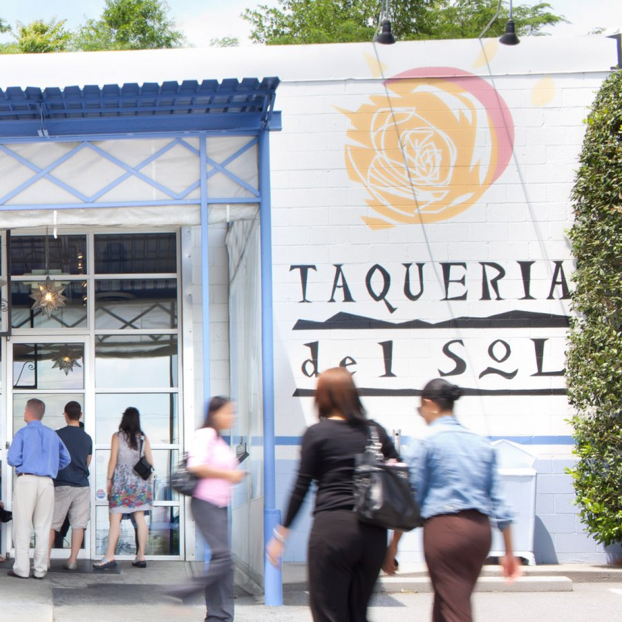 Taqueria del Sol restaurant facade with patrons in foreground