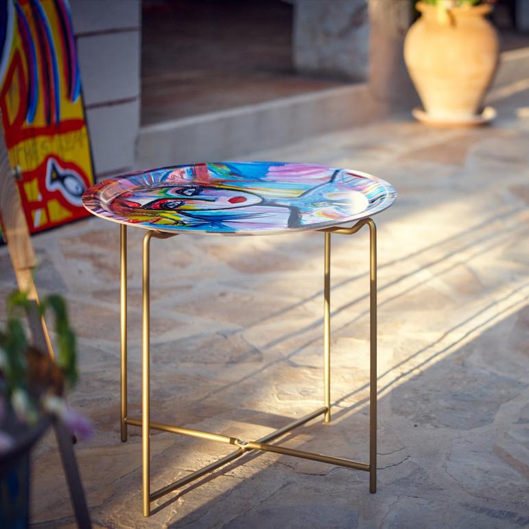 Gynning Design - Carolinas signum är ansiktena med särpräglade linjer och fjärilen som dyker upp överallt.Här blir konsten till funktionell inredning genom att placeras på bland annat brickbord och glas.