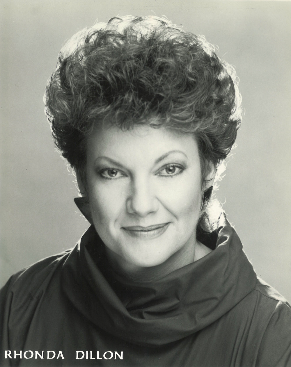 """Versatile singing actress, Rhonda Dillon, made her Broadway debut in 1988 in Sir Andrew Lloyd Webber's  The Phantom of the Opera.  She has subsequently appeared as both the prima donna """"Carlotta"""" and the ballet mistress """"Madame Giry"""" with every company in the United States! She holds a master's degree in choral conducting from the University of Southern California, where she toured Australia and New Zealand as a member of the USC Chamber Singers. She has sung with the LA Opera and was a featured nun in  The Firey Angel  by Prokovief. With the Los Angeles Master Chorale, she was a featured soloist at the Hollywood bowl. She toured the Western US as soloist with the Roger Wagner Chorale. Her voice can be heard on the soundtracks of such films as  Infidelity; Like Father Like Son; Burglar  and  Empire of the Sun.  Most recently Ms. Dillon created the role of Brenda in  Life Begins Again . Rhonda teaches at Cerritos College, El Camino College and College of the Canyons. She is on the board of NATS-Los Angeles as a director. Many of her students have won prestigious awards and are studying and teaching a new generation of singing artists!"""