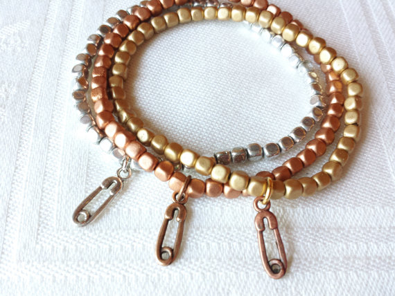 NONA DESIGN Safety Pin Charm stack bracelets in silver, yellow and rose gold gold, $10 Etsy.com