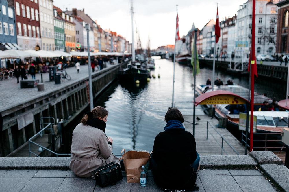 Enjoying a snack on the edge of the harbor overlooking historic Nyhavn.
