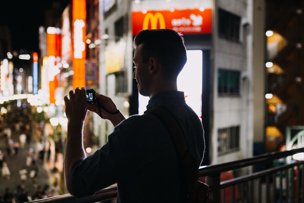 Silhouette of a man taking an iPhone photo in front of a McDonalds in Shinjuku Tokyo Japan