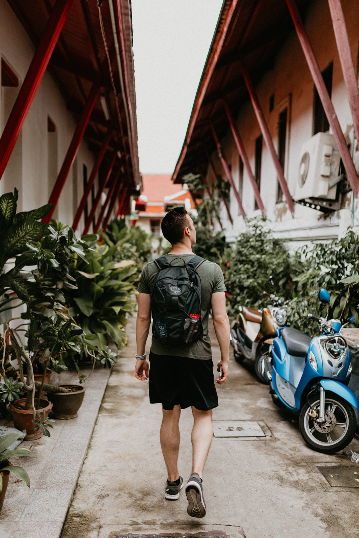 man walking towards Wat Arun with moped.jpg