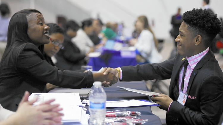 David Jeffries, a senior at Mather High School, shakes hands at the end of an interview with Northern Illinois University regional admissions counselor Christy Dorsey on Oct. 27, 2015, at the Chicago Scholars Foundation's 9th annual Onsite Admissions Forum and Luncheon at Navy Pier in Chicago. (Jose M. Osorio / Chicago Tribune)
