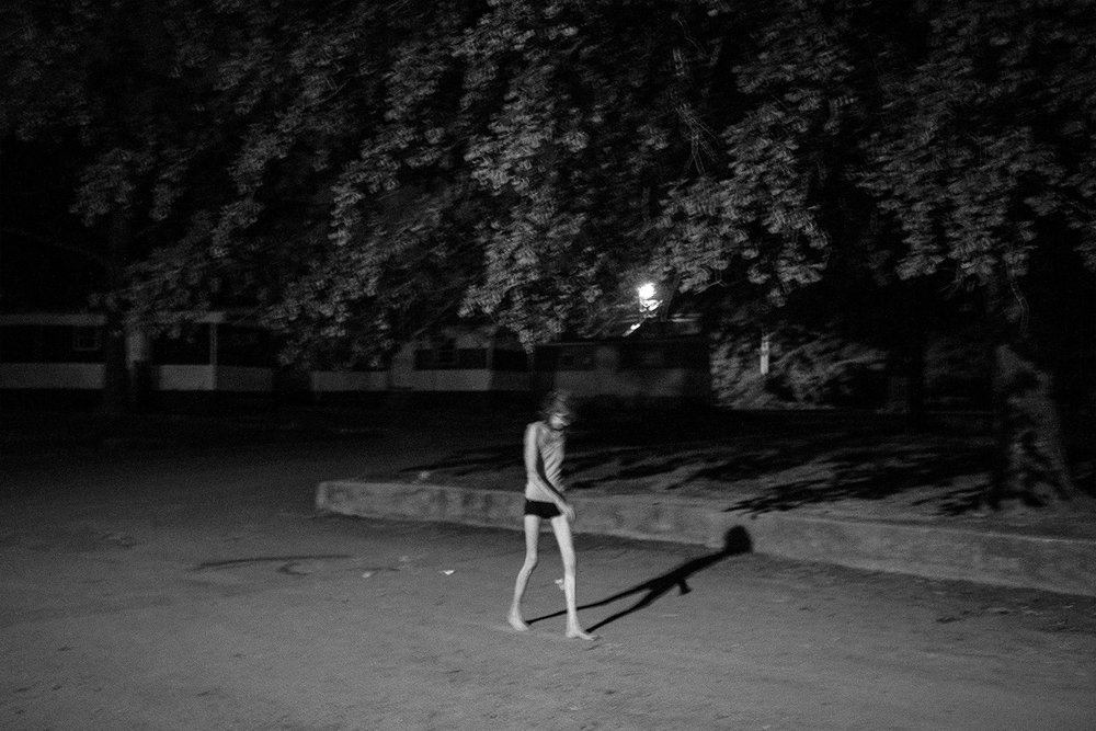 """Mama,"" takes a late-night walk through her trailer park. Mama is a meth and synthetic marijuana user with chronic health issues. She looks after people in the trailer park and can often be found cooking or comforting her neighbors. © Jared Ragland"