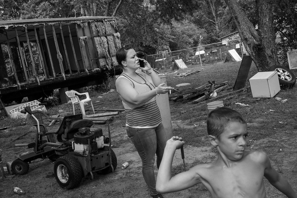 Misty, 30, argues with her sister over the phone while her son, Michael, throws knives. © Jared Ragland