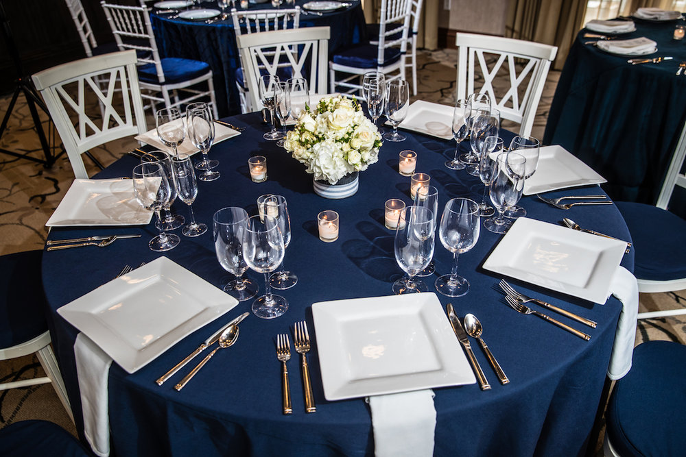 Clean and slightly nautical reception setting in navy blue and shades of white and cream.  Image by Eric McCallister Photography.