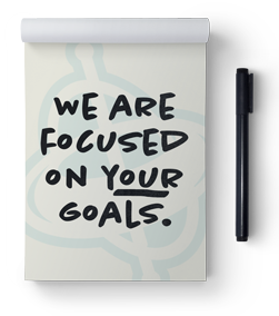 "Notepad with ""We are focused on your goals"" written on it."