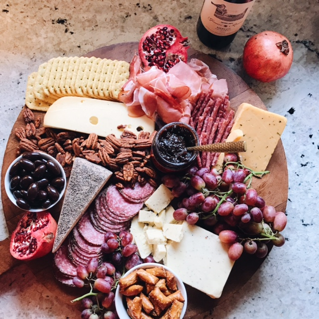 My charcuterie board made with their farmhouse cheddar with italian truffles, baby swiss, black pepper tosacano, chive cheddar, prosciutto, sliced pepper salami, salami sticks, grapes, pb pretzels, dark chocolate covered almonds, assorted crackers, fig butter and sliced pomegranate.