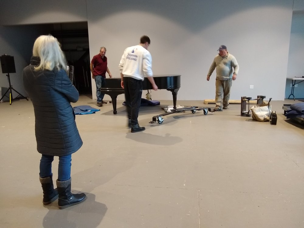 Penny Burke, the Center's former executive director, oversees installation of the piano in the Flex space. Dick Damon, tuner and piano mover, is in the background to Penny's right.