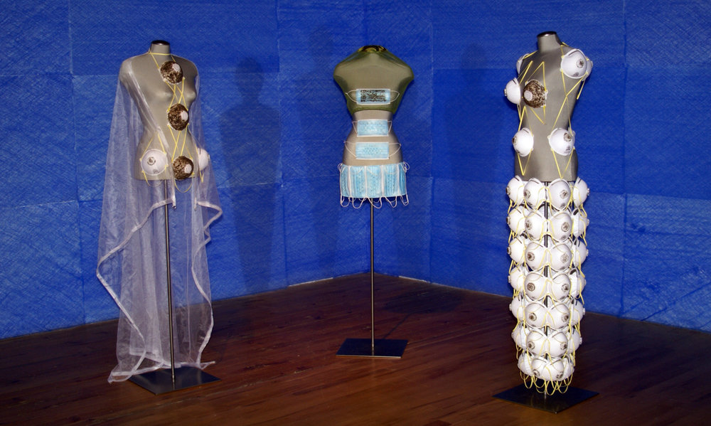 "Les Trois Manques - installation view      three mannequins, mosquito netting, N95 masks, surgical masks, mosquito netting, mosquitoes, 2 mirror spheres, grid wire, furnace filters  6' x 8' x 14""   2007"