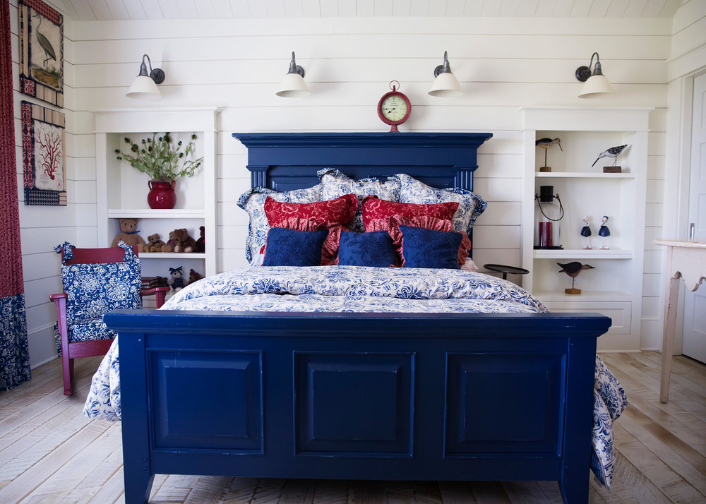 Red and blue bedroom with a quaint, farmhouse look   Resources:  Bed:  Thomasville Furniture Sconces:  Restoration Hardware Rocking Chair:  Antique Family Heirloom Bedding:  Ralph Lauren Home Collection  Design Thought:  In decorating bedrooms start with a bed skirt, then layer on sheets and a blanket, tucked in together.  Mix and match various patterns and colors.  Lay a folded duvet across the end of the bed.  At the head of the bed pile on the Euro shams and throw pillows in front of the sleeping pillows.
